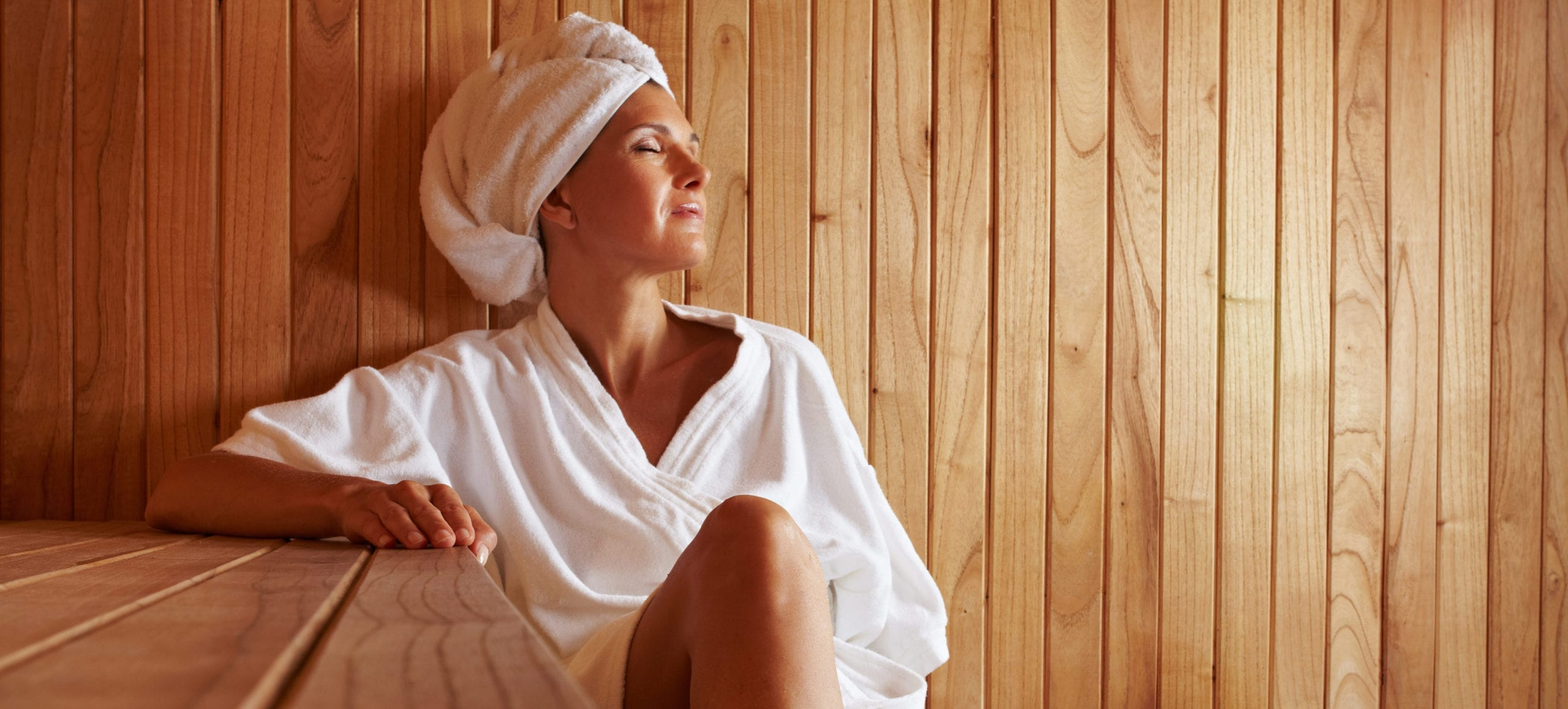 Woman in robe and towel on head in sauna relaxing with her eyes closed