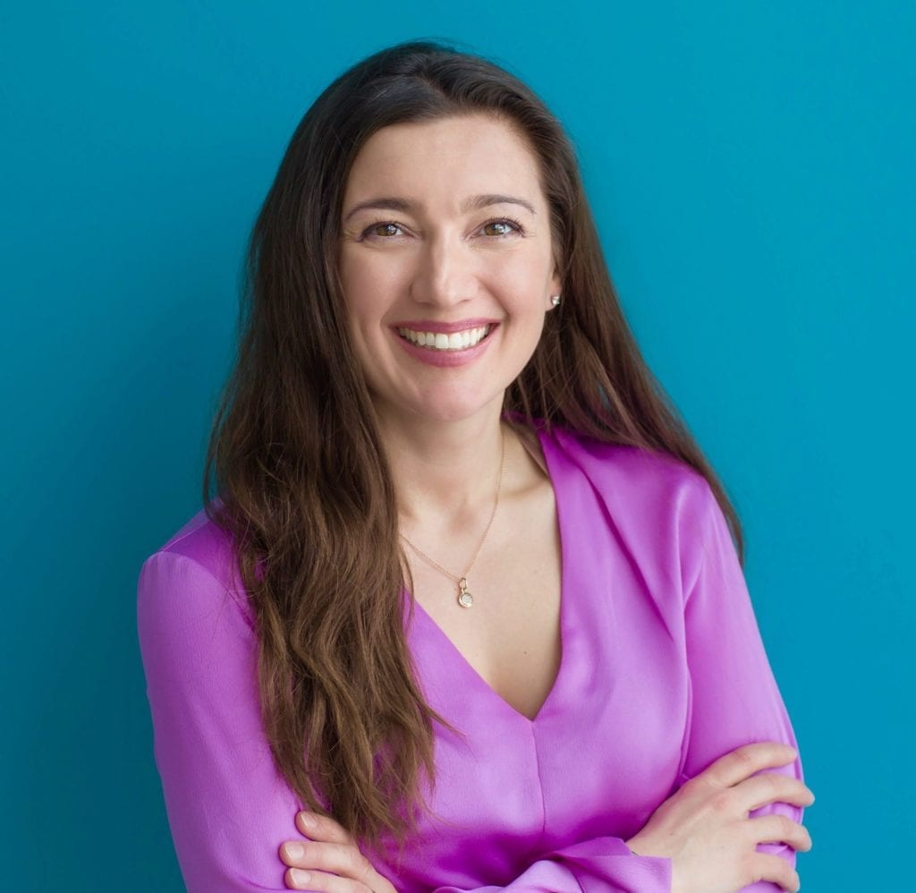 Dr. Emina Jasarevic headshot wearing pink blouse with long dark hair; learn more about our team