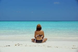 Woman in a bikini sitting on a beach with clear blue water and sky; highlighting managing anxiety