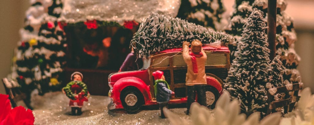 Model dad and children putting christmas tree on vehicle with snow, highlighting surviving the holidays