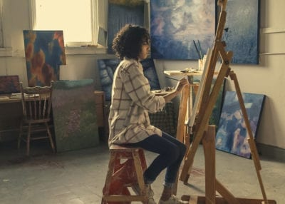 Teenage girl sitting infront of an easel painting with art in the background, highlighting the importance of art mindfulness on stress reduction and headaches in adolescents