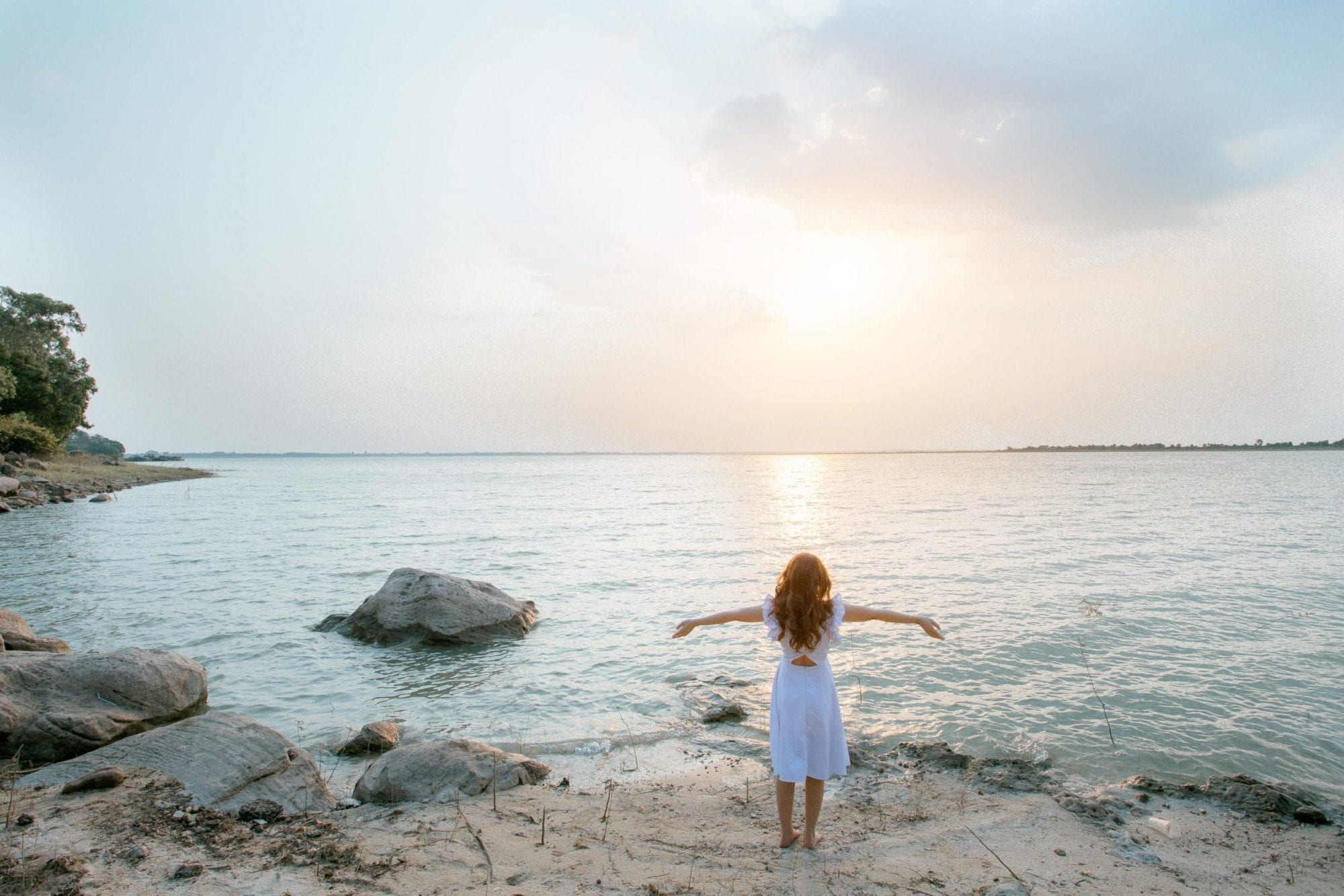 Woman with outstretched arms, facing the sun on the coast, having found chronic pain relief in neural therapy